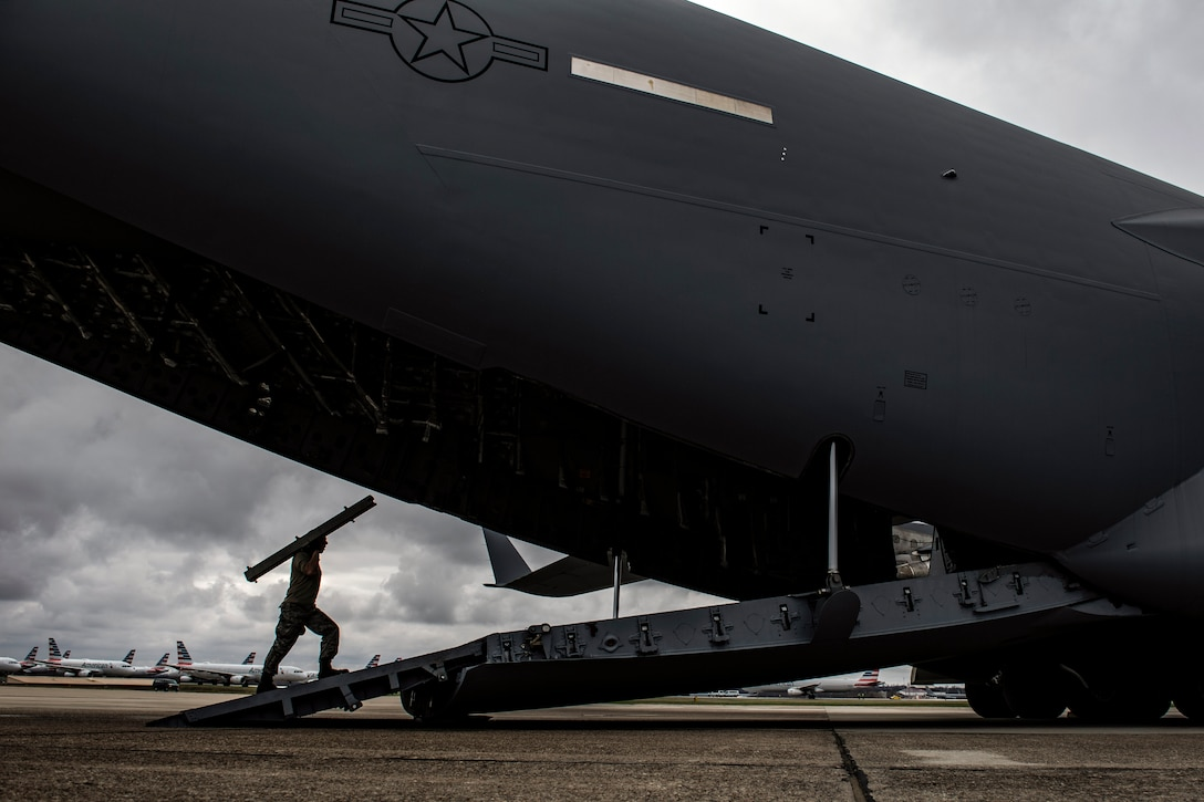 An airman walks up an open aircraft ramp balancing a long piece of equipment on his shoulders.