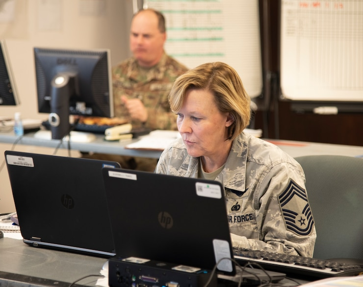 Woman in Airforce uniform types on a laptop.