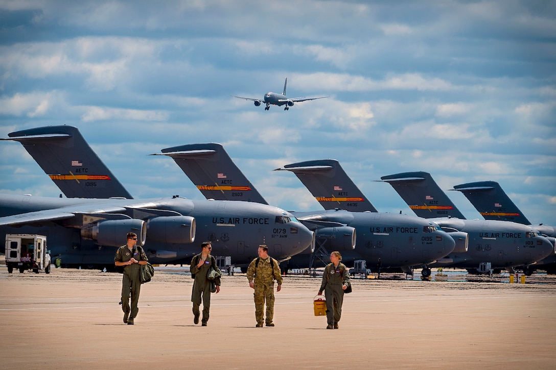 Four airmen walk on a flightline in front or a row of parked aircraft, as a plane flies overhead.