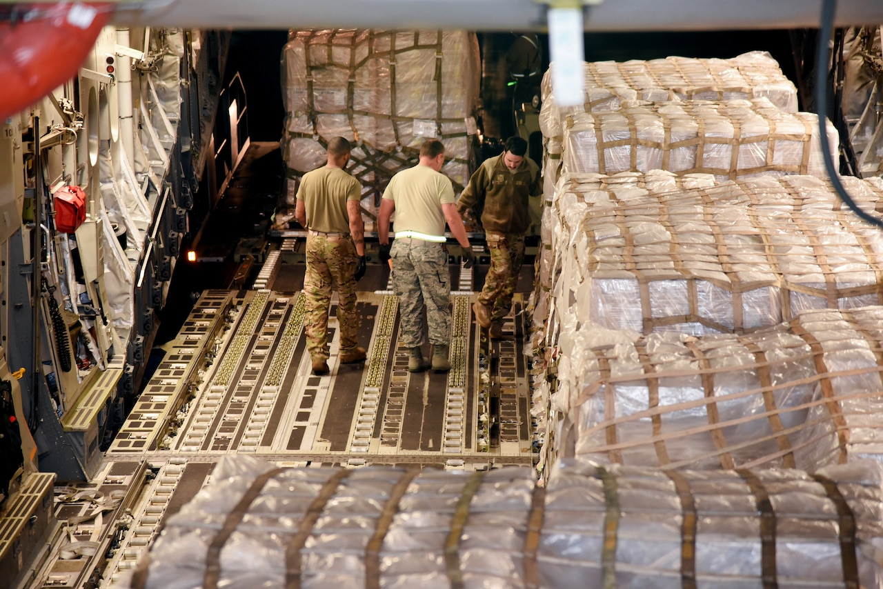 Service members in the cargo hold of an aircraft work with pallets that are wrapped in plastic and strapped down.