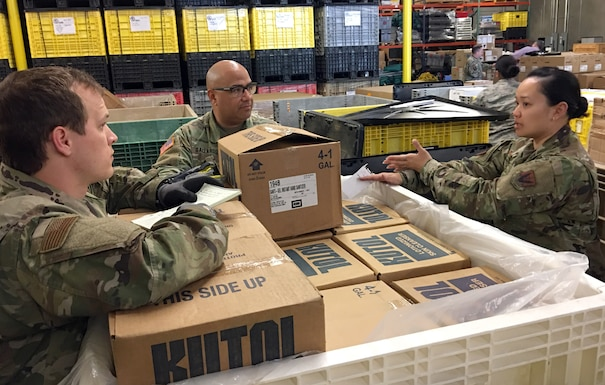 The California National Guard's Senior Airman Mikel Chatelle, 144th Fighter Wing, Army Staff Sgt. Ivan Gallardo, Medical Detachment, and Air Force Staff Sgt. Alice Nitzsche, 144th Fighter Wing, discuss plans on how to organize medical supplies for distribution at the California Emergency Medical Services Authority facility March 20, 2020 in Sacramento, California.