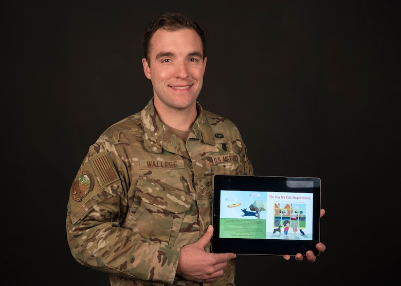 "Staff Sgt. Adam Wallace, 22nd Training Squadron water survival instructor, presents a digital copy of his newly self-published children's book ""The Day My Kids Stayed Home"" at Fairchild Air Force Base, Washington, April 1, 2020. Wallace conceptualized the book about a month ago at the start of the U.S. physical distancing efforts and turned out the completely illustrated text in just over two weeks. (U.S. Air Force photo Staff Sgt. Ryan Lackey)"