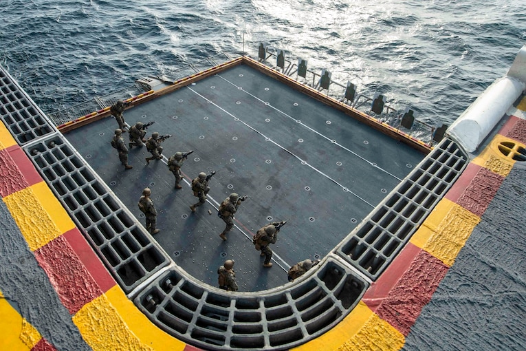 A row of Marines, seen from overhead, fire at targets on a ship deck.
