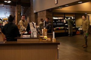 U.S. Airmen demonstrate social distancing while purchasing their food in the Iditarod Dining Facility on Joint Base Elmendorf-Richardson, Alaska, April 2, 2020. The dining facility used signs to remind people to maintain distance as a measure against COVID-19.