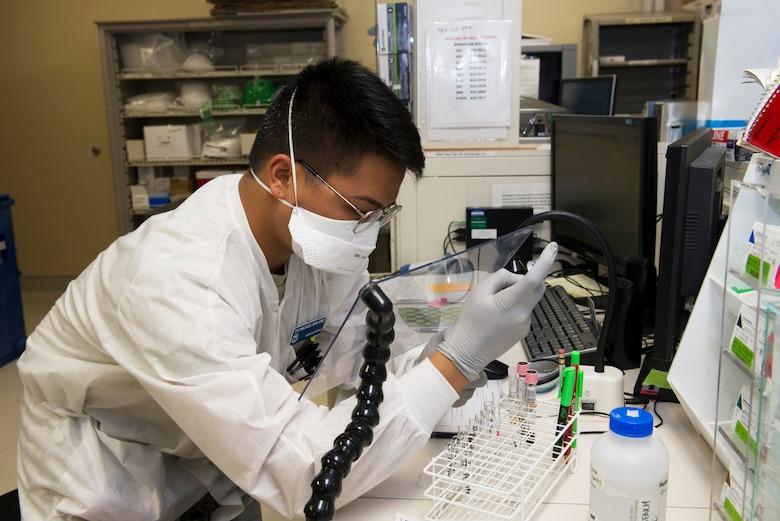 An airman performs lab testing