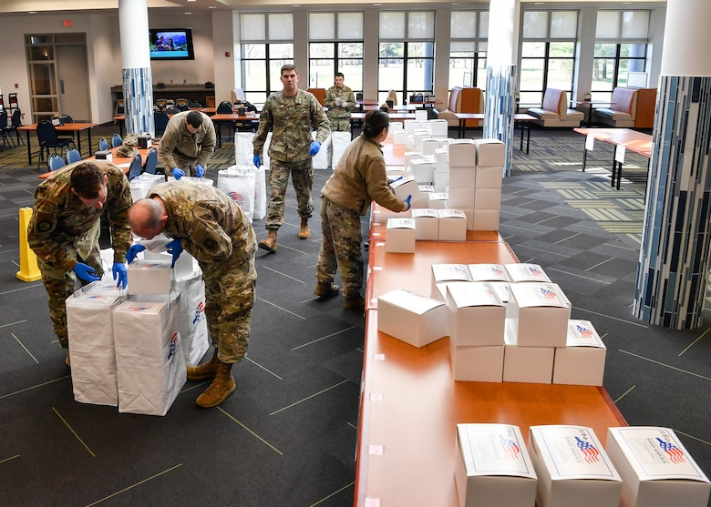 Airmen at the Halvorson Hall dining facility on Joint Base McGuire-Dix-Lakehurst, N.J., sort and pack lunches into appropriate bags that will be distributed to quarantined individuals across the installation April 2, 2020. Being the only source of nourishment during quarantine, 87th Force Support Squadron services Airmen create more than 150 meals each meal period to ensure each member is provided proper nourishment.