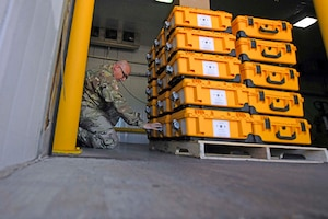 A soldier kneels next to a stack of packages.