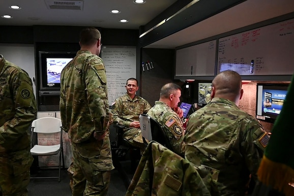 U.S. Army Capt. Jason Yankee, an operations officer assigned to the 115th Military Police Battalion, Maryland Army National Guard, discusses communications and command support to local and state agencies with his team while at FedEx Field parking lots in support of Prince George's County Department of Health's efforts to setup a COVID-19 medical screening center, March 25, 2019, in Landover, Maryland. The site will provide assistance as well as information for the citizens of Maryland and will operate by appointment only. (U.S. Air National Guard photo by Staff Sgt. Enjoli Saunders)