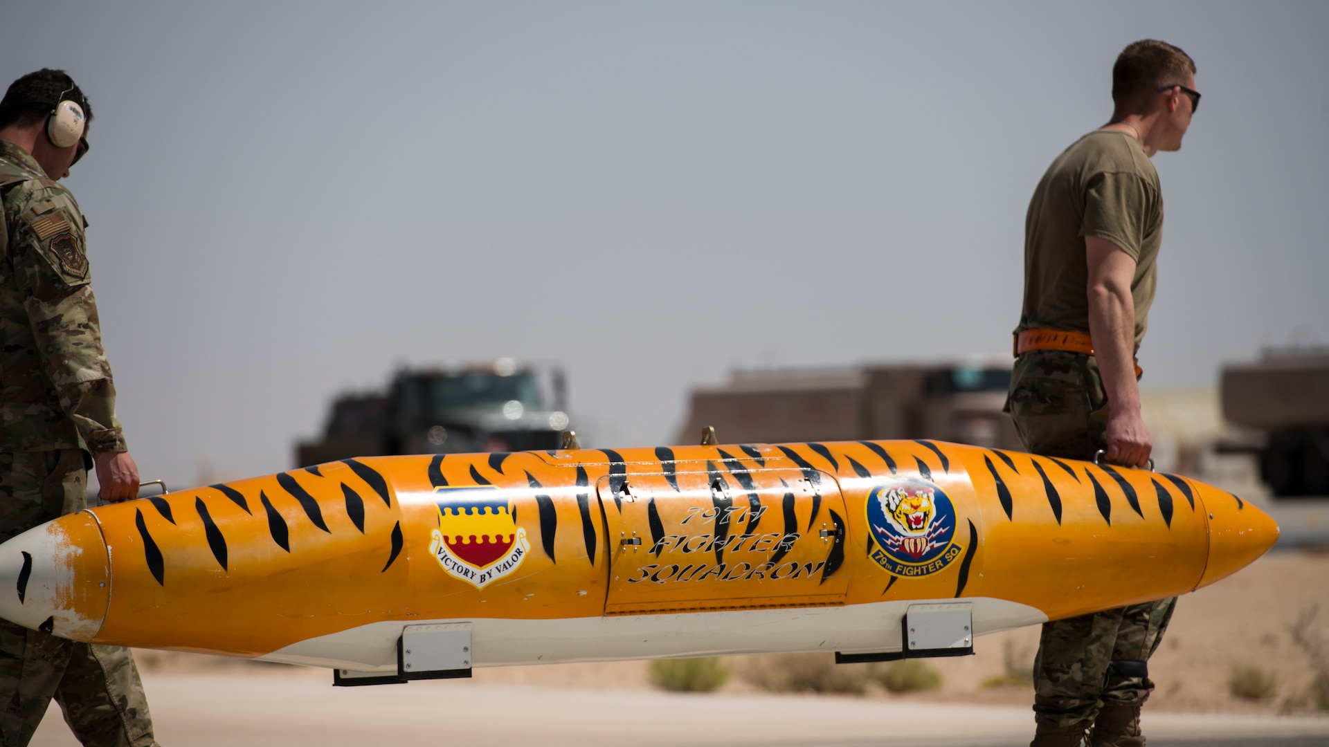 """Munitions systems specialists with the 380th Expeditionary Aircraft Maintenance Squadron transport a storage pod of a U.S. Air Force F-16 """"Viper"""" Fighting Falcon at an undisclosed location in the U.S. Central Command area of responsibility, Feb. 14, 2020."""