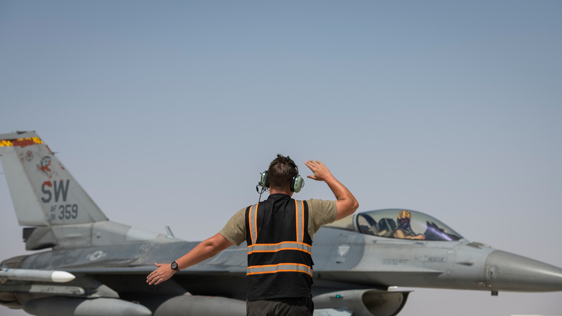 """U.S Air Force Senior Airman Steven Kuethe, a crew chief with the 380th Expeditionary Aircraft Maintenance Squadron marshals a U.S. Air Force F-16 """"Viper"""" Fighting Falcon assigned to the 79th Expeditionary Fighter Squadron at an undisclosed location in the U.S. Central Command area of responsibility, Feb. 14, 2020."""