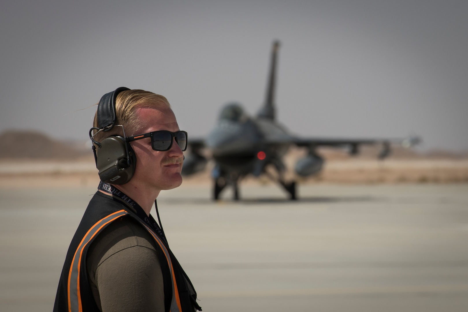 """U.S Air Force Staff Sgt. David Williams, a crew chief with the 380th Expeditionary Aircraft Maintenance Squadron prepares to marshal a U.S. Air Force F-16 """"Viper"""" Fighting Falcon assigned to the 79th Expeditionary Fighter Squadron at an undisclosed location in the U.S. Central Command area of responsibility, Feb. 14, 2020."""