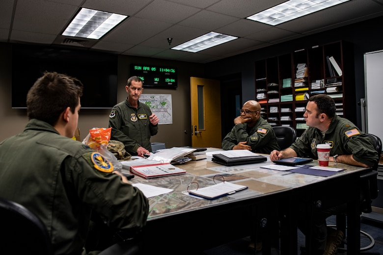 Col. John F. Robinson, 911th Airlift Wing commander, talks with other aircrew members at the Pittsburgh International Airport Air Reserve Station, Pennsylvania before transporting mobilized Airmen to Joint Base Mcguire-Dix-Lakehurst in support of the COVID-19 efforts, April 5, 2020.