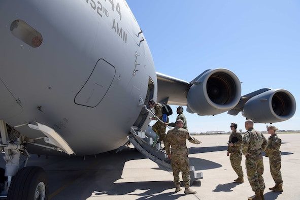 """Mobilized Air Force Reserve medics board a C-17 in route to """"hot zones"""" in support of the COVID-19 pandemic from Luke Air Force Base, Ariz., April 5, 2020. This deployment is part of a larger mobilization package of more than 120 doctors, nurses and respiratory technicians Air Force Reserve units across the nation provided over the past 48 hours in support of the COVID-19 response to take care of Americans. The C-17 is deployed from March Air Force Base, Calif."""