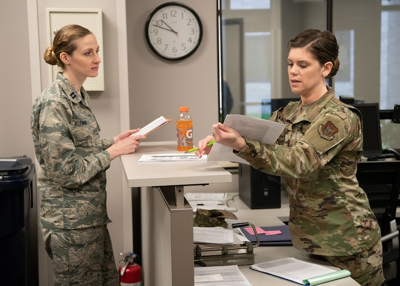 Capt. Kristina Fleming, 445th Aeromedical Staging Squadron Registered Nurse, out processes with Master Sgt. Jessica Pruitt, 445th Force Support Squadron, here April 5, 2020. She and medical personnel from the 445th Airlift Wing's Aerospace Medicine and Aeromedical Staging Squadrons were notified April 4, 2020 that they would be mobilized to New York City to help with the COVID-19 pandemic. The Citizen Airmen will join other military personnel providing medical services at the Jacob Javits Center in New York City. This deployment is part of a larger mobilization package of more than 120 doctors, nurses and respiratory technicians Air Force Reserve units across the nation provided over the past 48 hours in support of COVID-19 response to take care of Americans. (U.S. Air Force photo/Mr. Patrick O'Reilly)