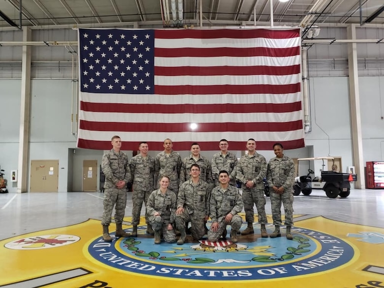 A large group photo with U.S. Air Force Airman 1st Class Kayla Jerido, 86th Civil Engineer Squadron fire protection apprentice, far right, posing with her classmates after graduating from the Louis F. Garland Department of Defense Fire Academy at Goodfellow Air Force Base, Texas, July 15, 2018.