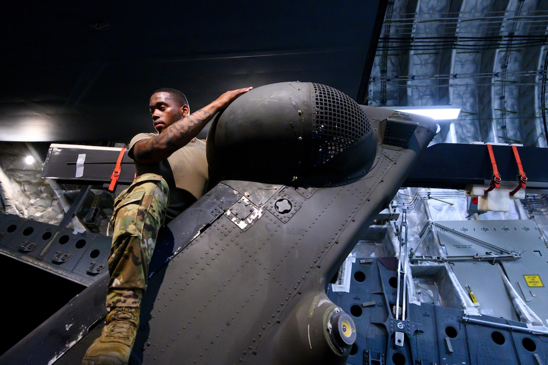 U.S. Army Spc. Devante Turner, 82nd Combat Aviation Brigade (CAB), 3rd Battalion crew chief, assists in unloading a UH-60 Black Hawk helicopter off a U.S. Air Force 21st Airlift Squadron C-17 Globemaster III aircraft
