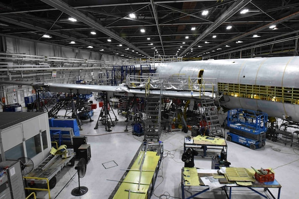 An aircraft sits broken down in a industrial facility.