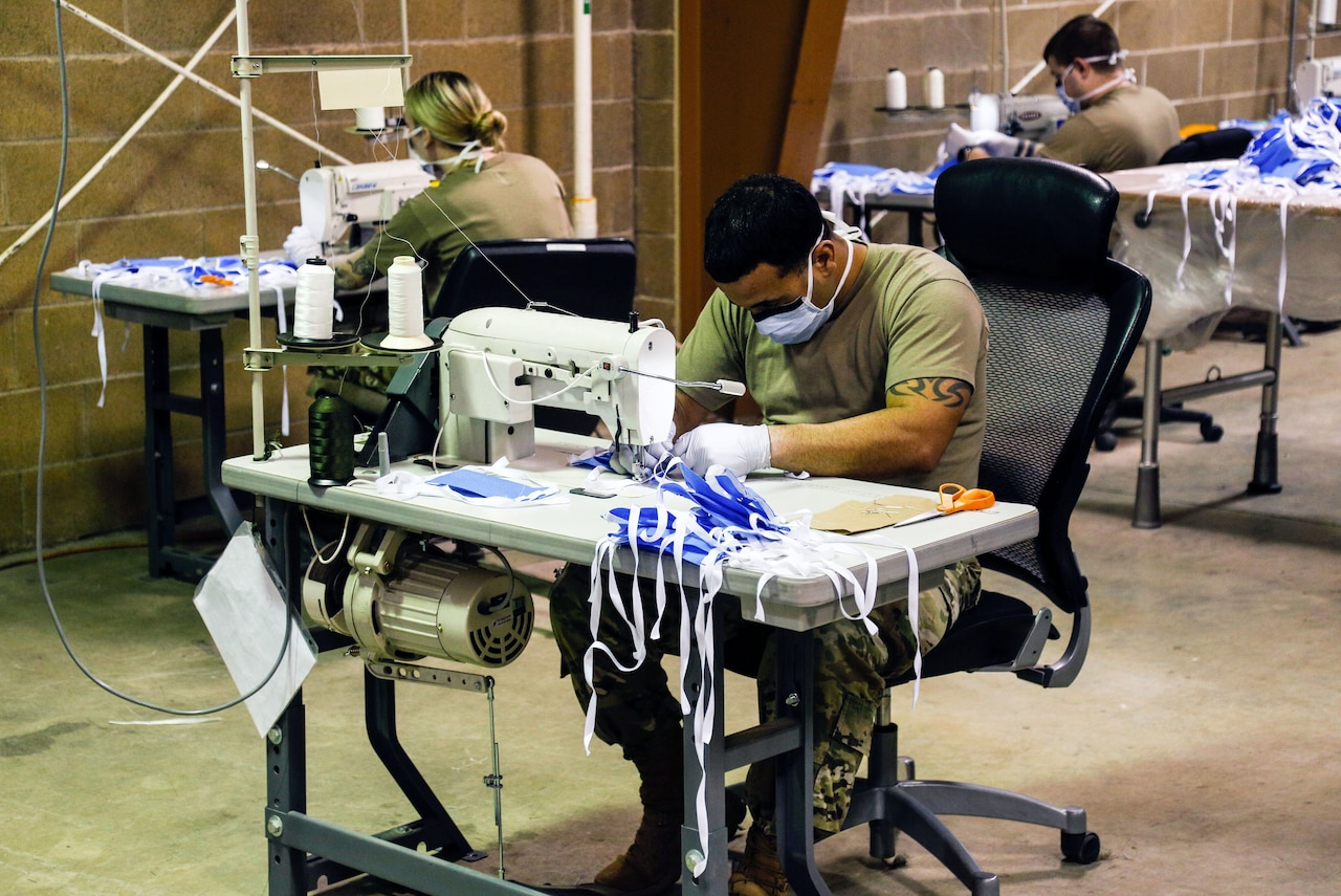 Soldiers use sewing machines to make surgical masks for patients.