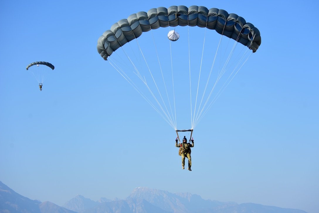Two airmen parachute to the ground against a blue sky.