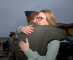 Staff Sgt. Geoffrey Brunelle, 433rd Airlift Wing medical technician, hugs his wife goodbye before departing Joint Base San Antonio-Lackland, Texas, to respond to the COVID-19 crisis April 5, 2020.