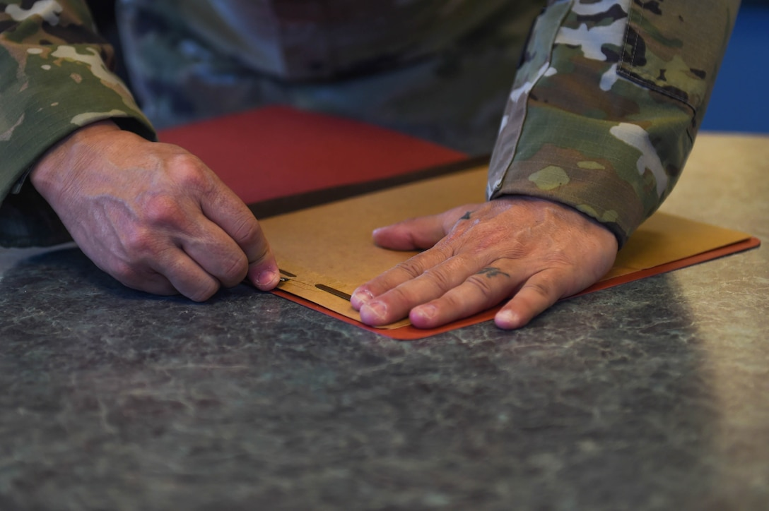 Senior Master Sgt. Samuel Cole, 62nd Operations Support Squadron superintendent, uses a razor to carefully remove the metal strip from a folder to produce cloth face masks at the 62nd OSS aircrew flight equipment fabrication shop on Joint Base Lewis-McChord, Wash., April 6, 2020. The metal strips were sewn into the part of the mask that goes over the nose to make it more form-fitting and create more of a seal. (U.S. Air Force photo by Airman 1st Class Mikayla Heineck)
