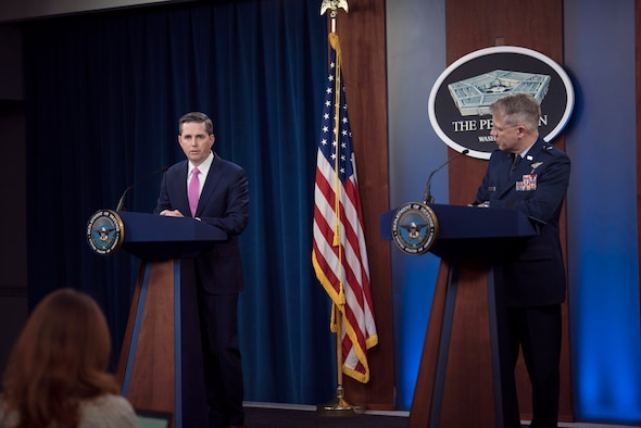 A civilian and an airman stand at lecterns.