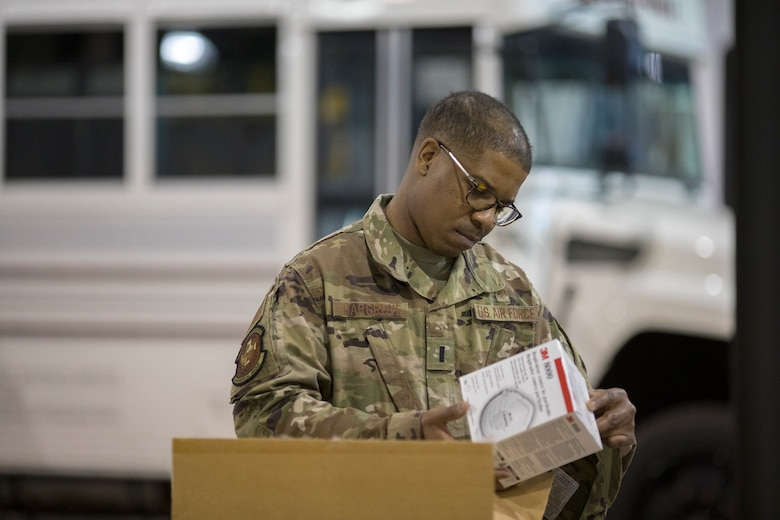 U.S. Air Force 1st Lt. Tyrell Hargrove with the Delaware National Guard inspects personal protective equipment inside Delaware Emergency Management Agency headquarters, Smyrna, Del., March 27, 2020. Hargrove is helping evaluate sites that can be used as acute care facilities should hospitals become overwhelmed with COVID-19 patients.