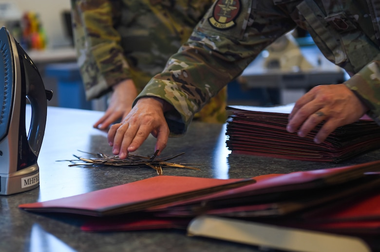 Senior Master Sgt. Samuel Cole, 62nd Operations Support Squadron superintendent, reaches for a pile of metal strips taken from folders to produce cloth face masks at the 62nd OSS aircrew flight equipment fabrication shop on Joint Base Lewis-McChord, Wash., April 6, 2020. The metal strips were sewn into the part of the mask that goes over the nose to make it more form-fitting and create more of a seal. (U.S. Air Force photo by Airman 1st Class Mikayla Heineck)
