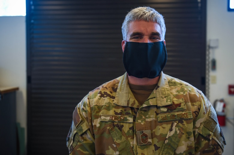 Chief Master Sgt. Skip Hurley, 62nd Operations Group chief enlisted manager, poses with a completed cloth face mask in the 62nd Operations Support squadron aircrew flight equipment fabrication shop on Joint Base Lewis-McChord, Wash., April 6, 2020. Mask production is not what the 62nd OSS AFE fabrication shop normally produces, but the unit innovatively adjusted to the mission requirements due to the COVID-19 outbreak. (U.S. Air Force photo by Airman 1st Class Mikayla Heineck)