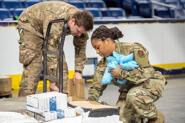 Two Air National Guardsmen sort medical supplies.