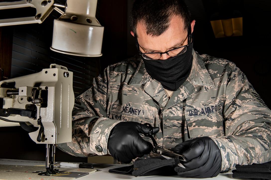 An aircraft flight equipment technician cutting material to make a cloth face mask.