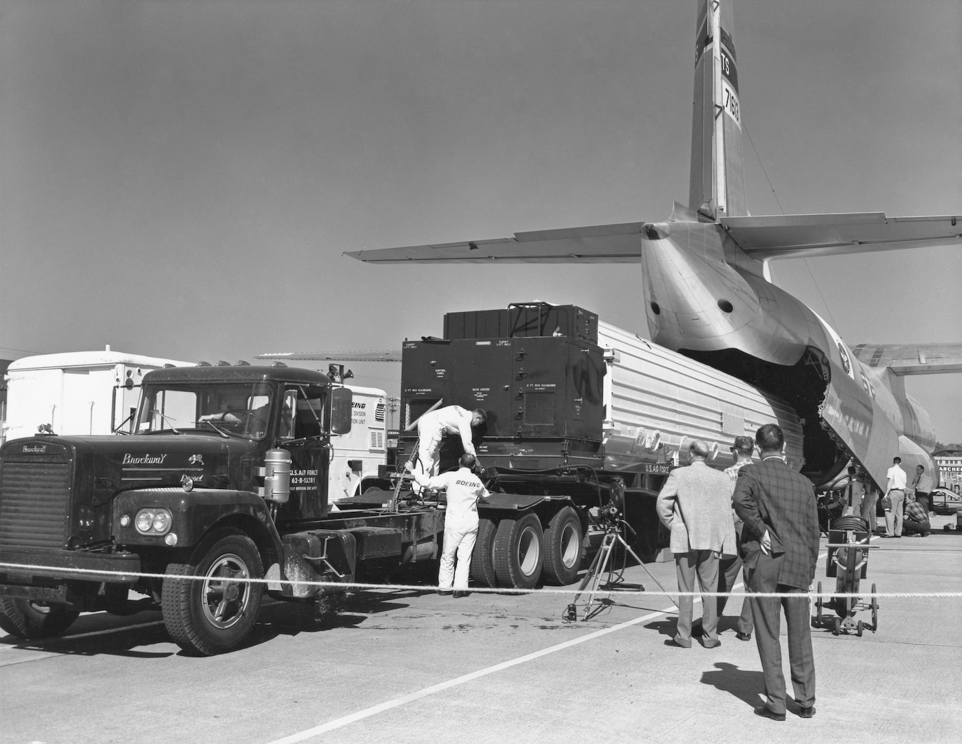 Personnel loading a Minuteman missile into the back of a C-133B aircraft.