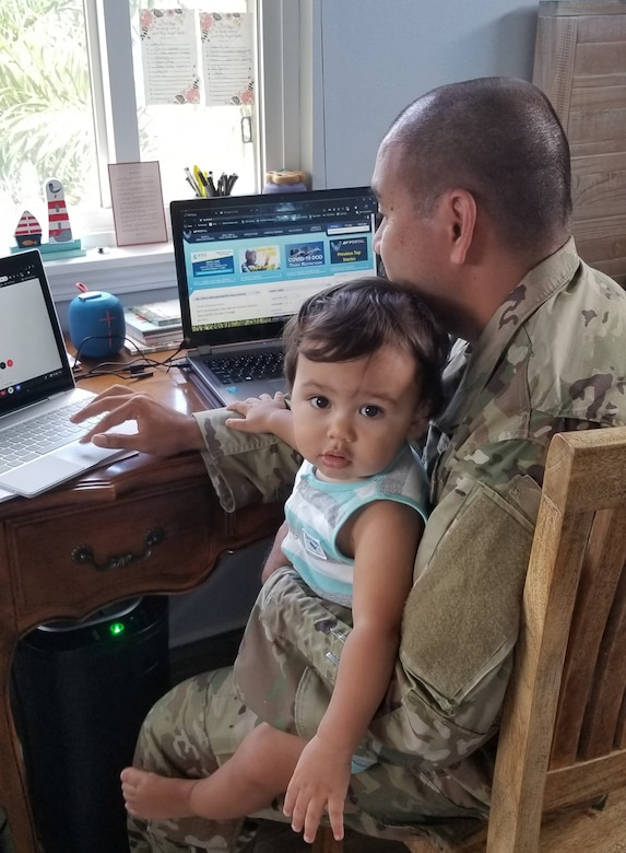 Staff Sgt. Charlie Trilles, a 624th Civil Engineer Squadron engineering journeyman, teleworks with his 1-year-old son, Evan, on his lap during the 624th Regional Support Group virtual unit training assembly in April. (Courtesy Photo)