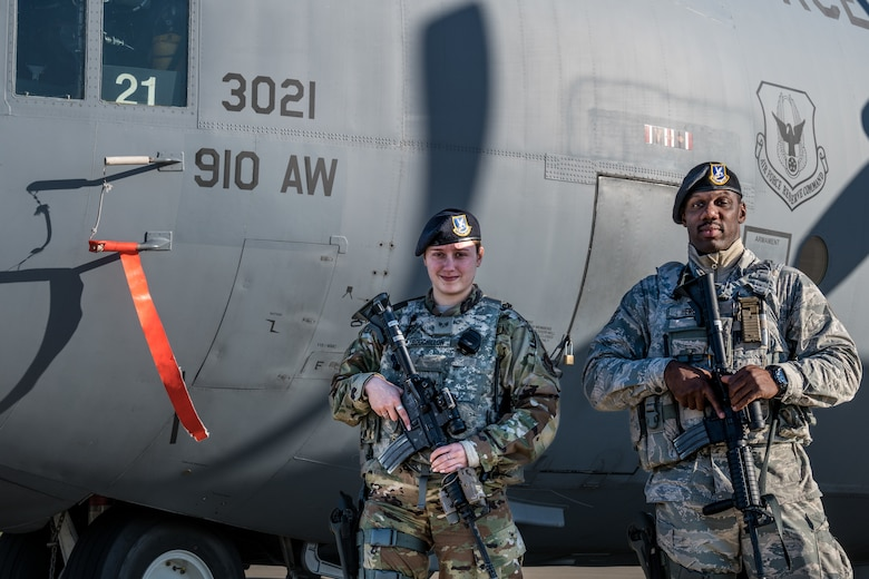 Senior Airman Alexandra Bouchillon and Staff Sgt. Justin Herod, fireteam members assigned to the 910th Security Forces Squadron, stand guard by a C-130H Hercules aircraft on the Youngstown Air Reserve Station, Ohio, flightline. (Senior Airman Noah J. Tancer)