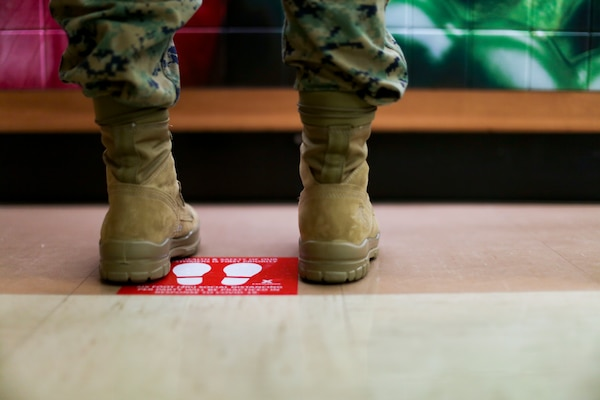 A service member stands by a red sign with footprints on the floor.