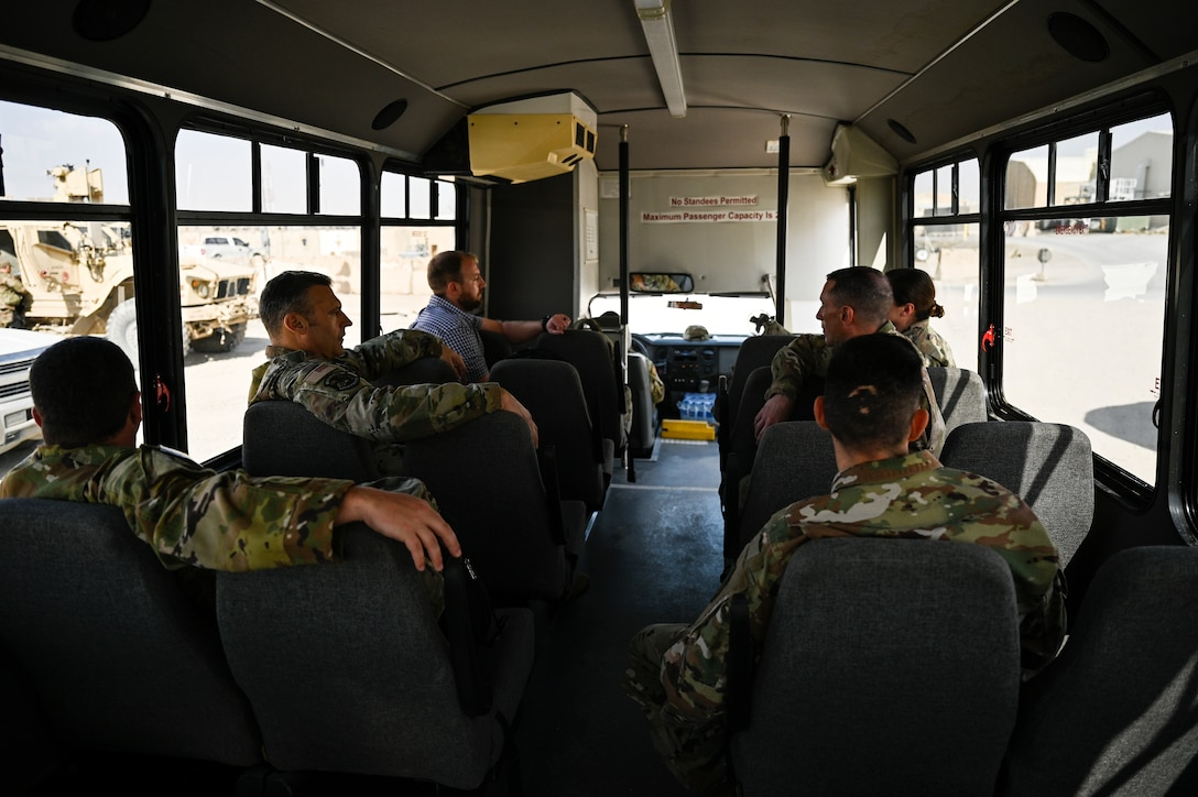 U.S. Air Force Lt. Gen. Joseph T. Guastella, Jr., Commander, U.S. Air Forces Central Command and Combined Forces Air Component Commander, and U.S. Air Force Chief Master Sgt. Shawn L. Drinkard, Command Chief Master Sgt. for USAFCENT, ride a bus on Kandahar Airfield, Afghanistan during a visit to the 451st Air Expeditionary Group, based at KAF to talk about the importance of the USAFCENT mission in Afghanistan, Feb. 24, 2020.