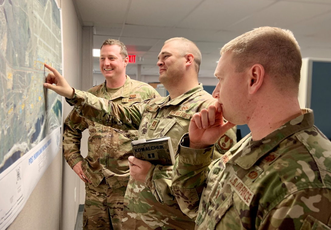 From left, Capts. Zach Bierhaus, Kyle Kowalchuk and Will Page discuss rebuild plans for both the flightline and support districts on Tyndall AFB, Fla.
