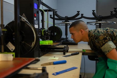 U.S. Marine Corps Cpl. Michael Espinosa with Makerspace, 2nd Marine Logistics Group monitors 3-D printing of face masks on Camp Lejeune, N.C., March, 2020. Marines from Makerspace utilized 3-D printing to rapidly manufacture personal protective equipment to be sent to aid FEMA Region 8 and 2nd Medical Battalion in COVID-19 screening. (U.S. Marine Corps photo by Lance Cpl. Scott Jenkins)