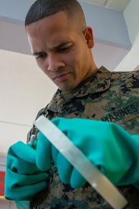 U.S. Marine Corps Cpl. Michael Espinosa with Makerspace, 2nd Marine Logistics Group quality checks a 3-D printed face mask on Camp Lejeune, N.C., March, 2020. Marines from Makerspace utilized 3-D printing to rapidly manufacture personal protective equipment to be sent to aid FEMA Region 8 and 2nd Medical Battalion in COVID-19 screening. (U.S. Marine Corps photo by Lance Cpl. Scott Jenkins)