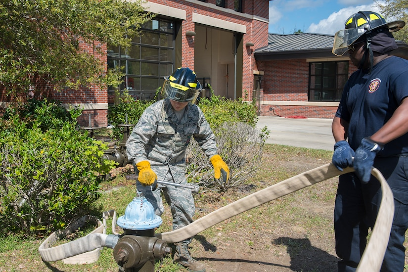 Latavis Johnson, right,  and Senior Airman Jacob Tripaldi, left, firefighters assigned to the 628th Civil Engineering Squadron Fire Department, attach a hose to a fire hydrant in Hunley Park-Air Base housing on Joint Base Charleston, S.C., March 25, 2020. The Fire Department is still conducting normal operations. Firefighters are taking preventative measures such as cleaning common areas every four hours, and enforcing higher hygiene standards like frequently washing hands.