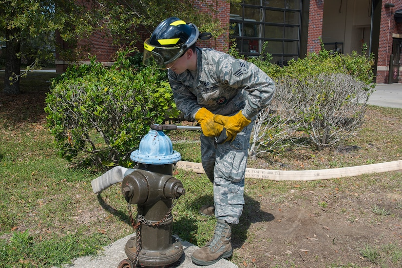 Senior Airman Jacob Tripaldi, a firefighter assigned to the 628th Civil Engineering Squadron Fire Department, works to open a fire hydrant after attaching a hose in Hunley Park-Air Base housing on Joint Base Charleston, S.C., March 25, 2020. The Fire Department is still conducting normal operations. Firefighters are taking preventative measures such as cleaning common areas every four hours, and enforcing higher hygiene standards like frequently washing hands.