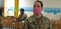1st Sgt. Rachael Fleharty-Strevig, Headquarters and Service Company, 3643d Brigade Support Battalion, New Hampshire National Guard, sorts through dry goods at the N.H. Food Bank in Manchester.