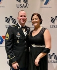 White male in dress uniform stands with white female in black dress with silver belt in front of white background with blue and red and blue eagles that say USAA.