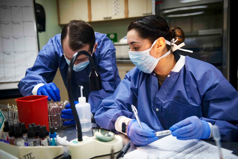 Two Navy medical technicians in personal protective equipment handle vials in a laboratory.