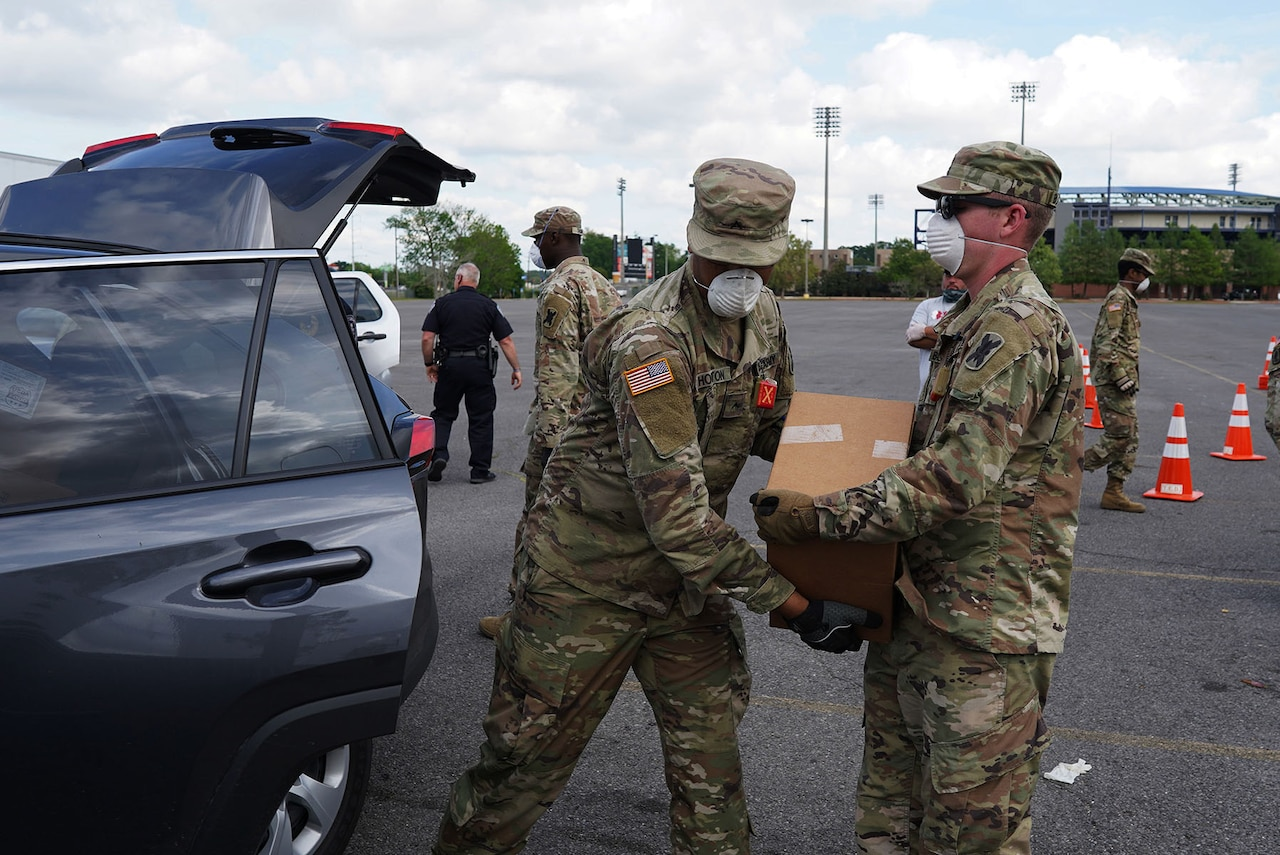 Two Guardsmen dressed in fatigues, and wearing protective face masks, unload boxes from a vehicle in a large parking lot.