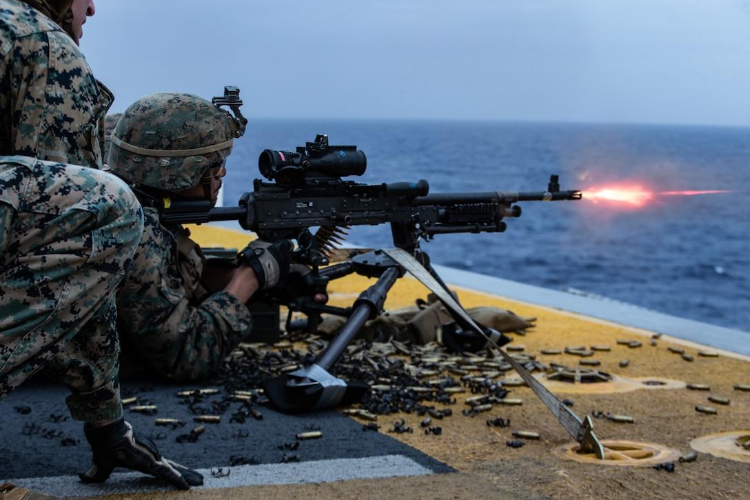 A Marine fires an M240B medium machine gun during a full mission profile defense of the amphibious task force exercise aboard amphibious assault ship USS America (LHA 6).
