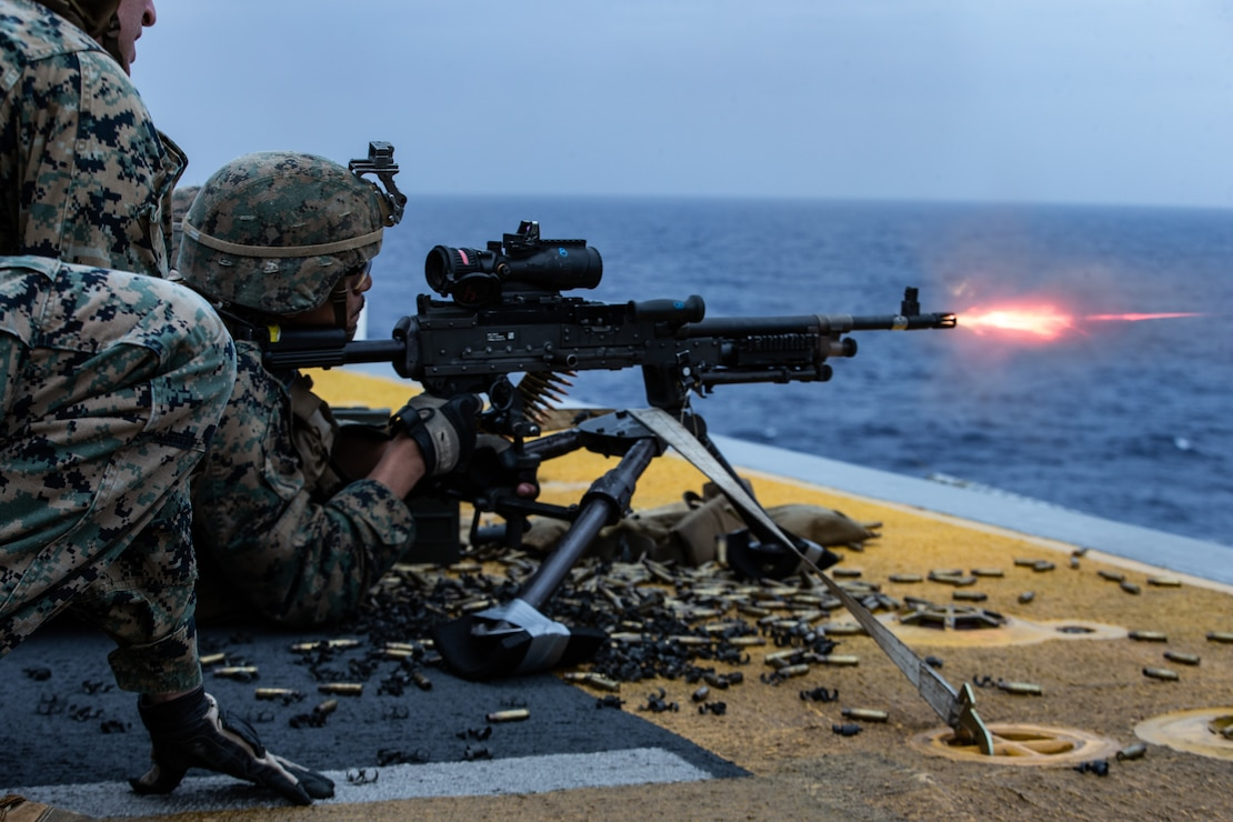 A Marine fires an M240B medium machine gun during a full mission profile defense of the amphibious task force exercise aboard amphibious assault ship USS America (LHA 6), March 28.