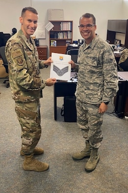 U.S. Air Force Col. Steve Snelson (left) the 6th Air Refueling Wing commander, presents a certificate to Airman 1st Class Shannon Bowman (right) a 6th ARW photojournalist, March 17, 2020, at MacDill Air Force Base, Fla.
