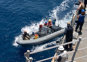 U.S. Navy Sailors assigned to Arleigh Burke-class guided-missile destroyer USS Kidd (DDG 100) depart in a rigid-hull inflatable boat (RHIB)