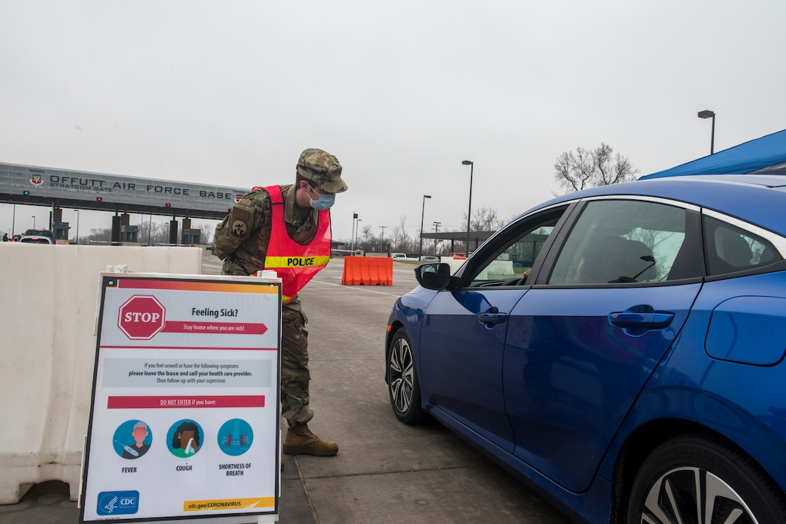A service member standing behind a COVID-19 symptoms sign bends down to look inside a car and ask the driver if they are experiencing any symptoms.